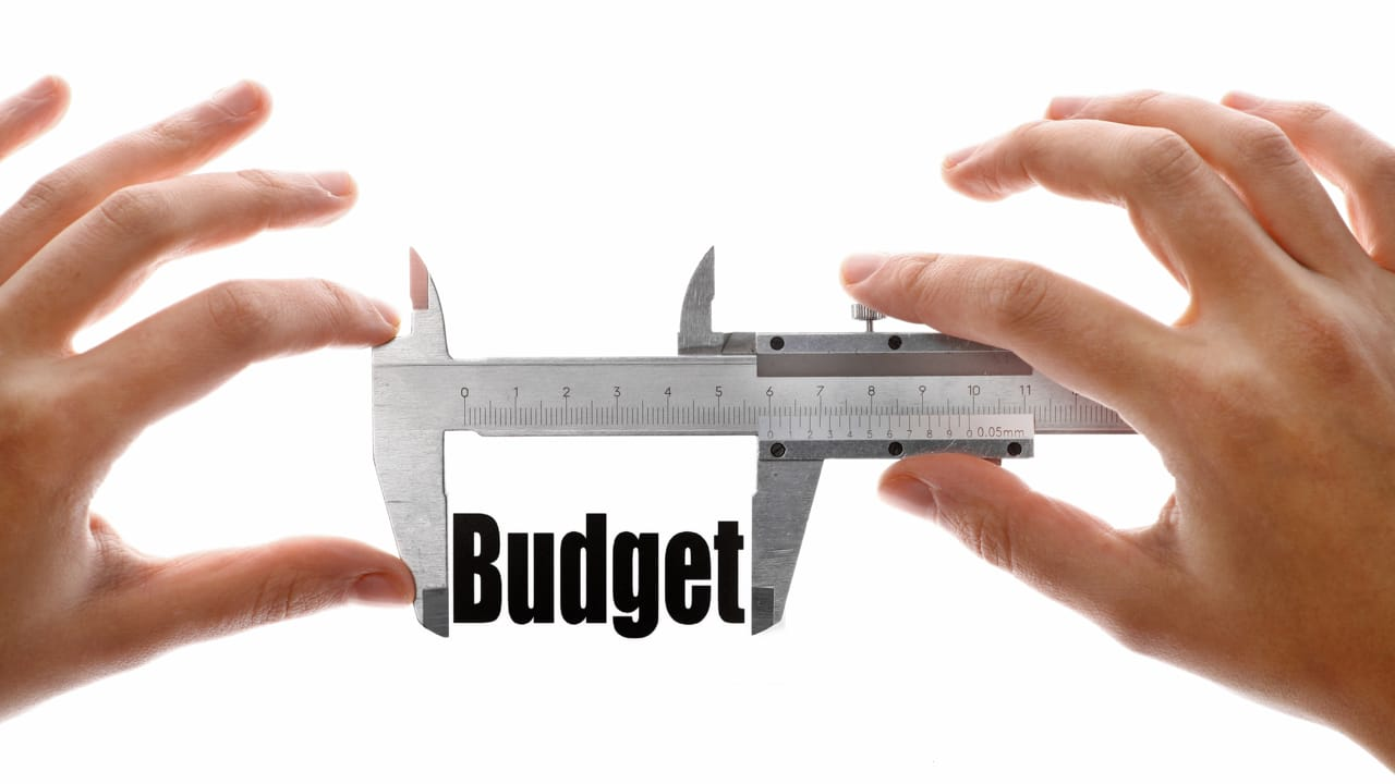"""Close up shot of two hands holding a caliper and measuring the word """"Budget"""""""